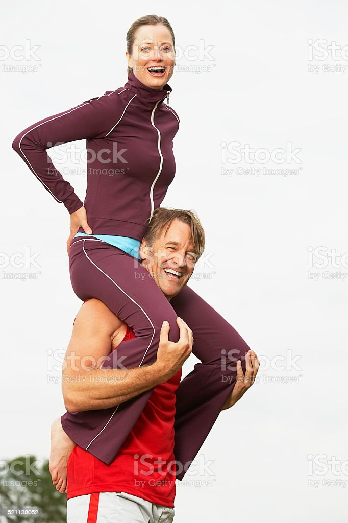 Man carrying woman piggyback on shoulders stock photo