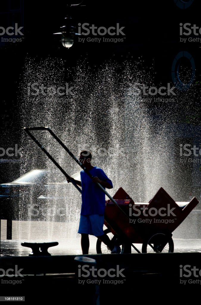 Man Carting Rickshaw in Front of Fountain royalty-free stock photo