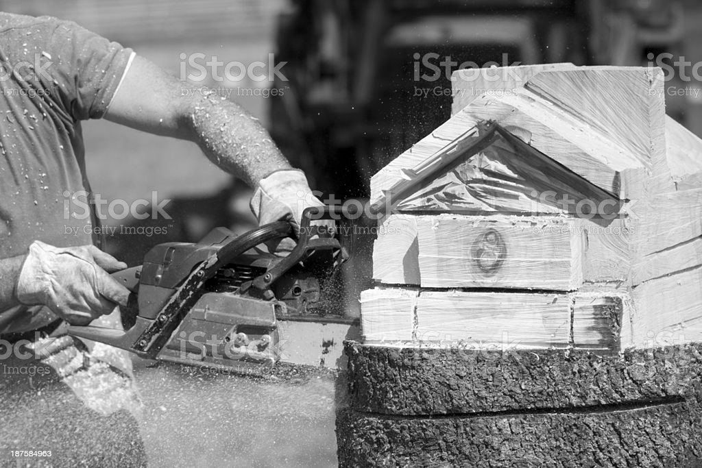 Man Carving A House With Chainsaw royalty-free stock photo