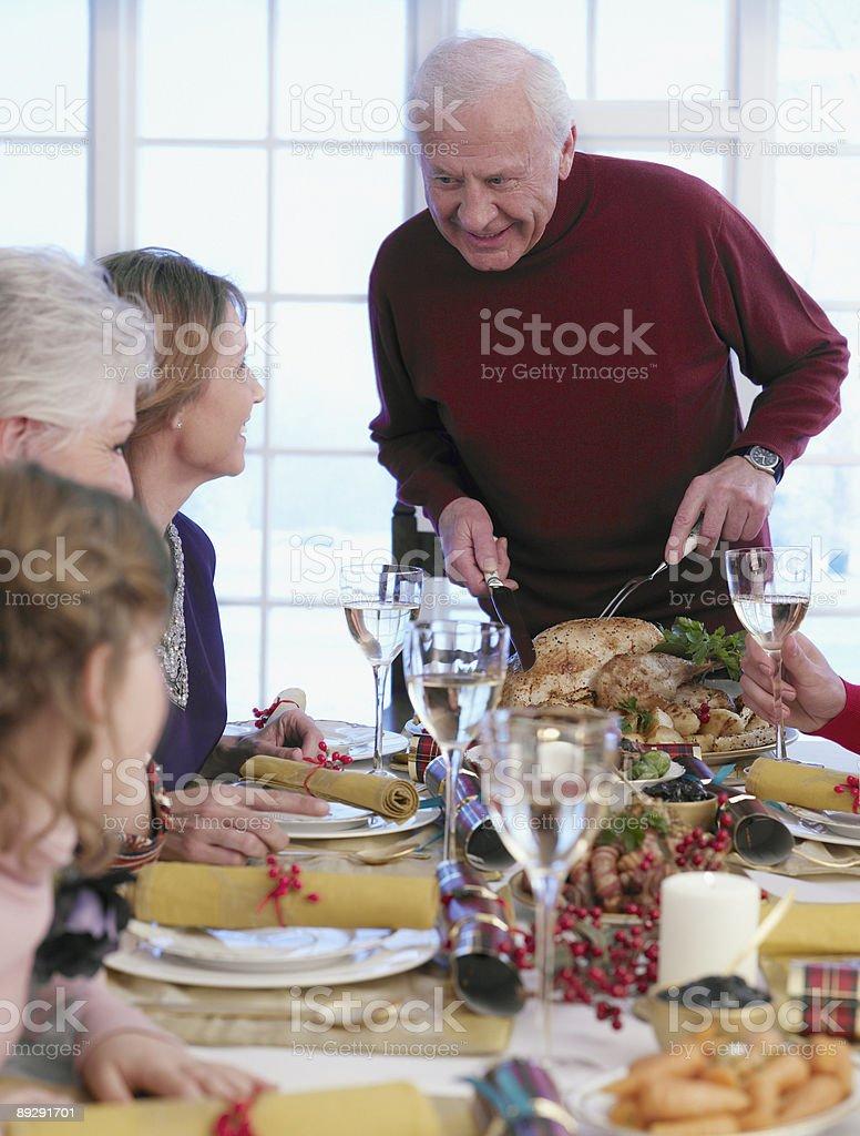 Man carving Christmas turkey at table royalty-free stock photo