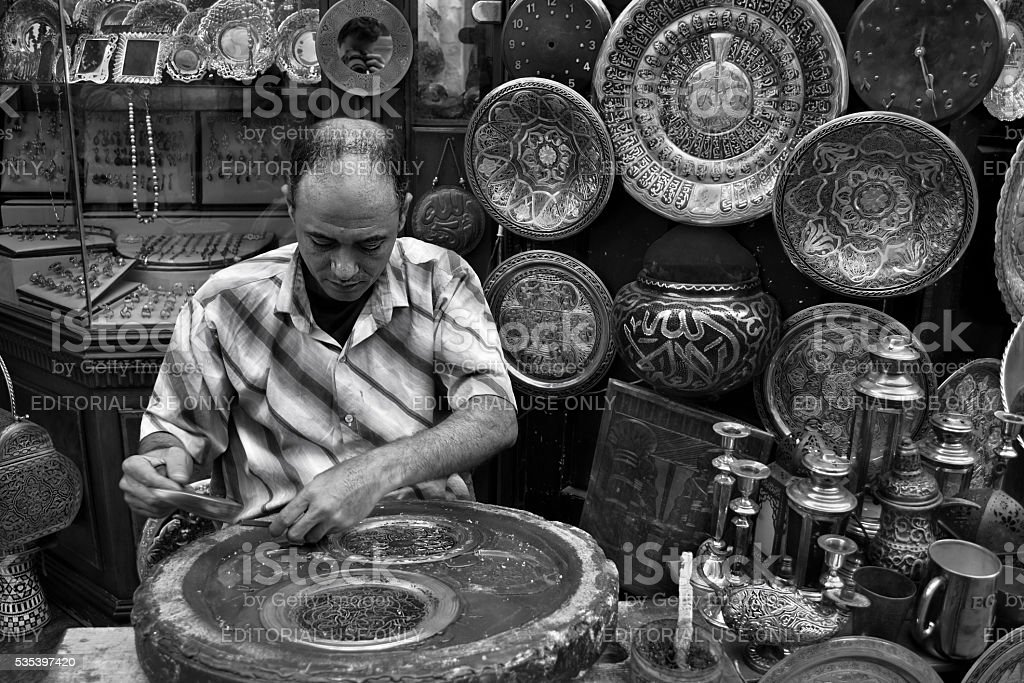 Man carving metal plates in old Cairo stock photo