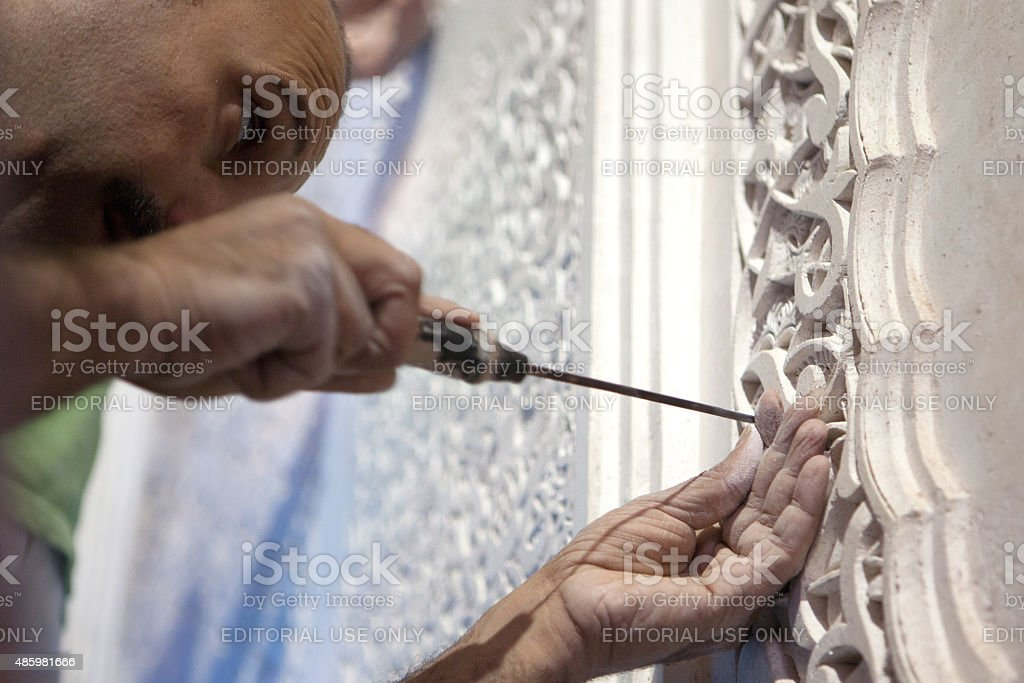 Man carving plaster on a building in Fez Morocco stock photo