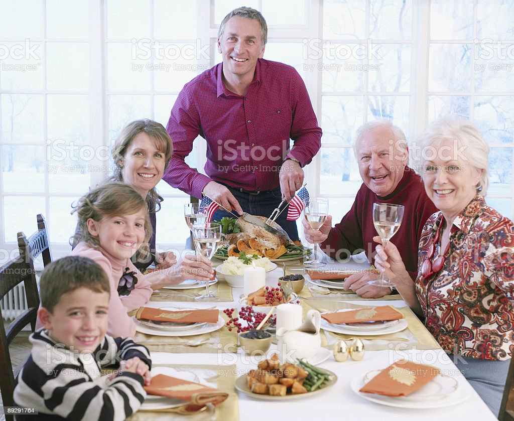 Man carving turkey for multi-generation family at table stock photo