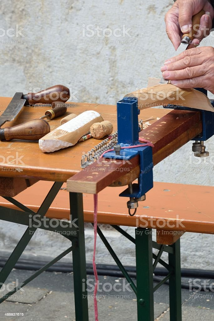 Man carving wood on bench stock photo