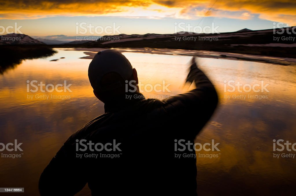 Man Casting a Fly Fishing Rod at High Alpine Lake stock photo