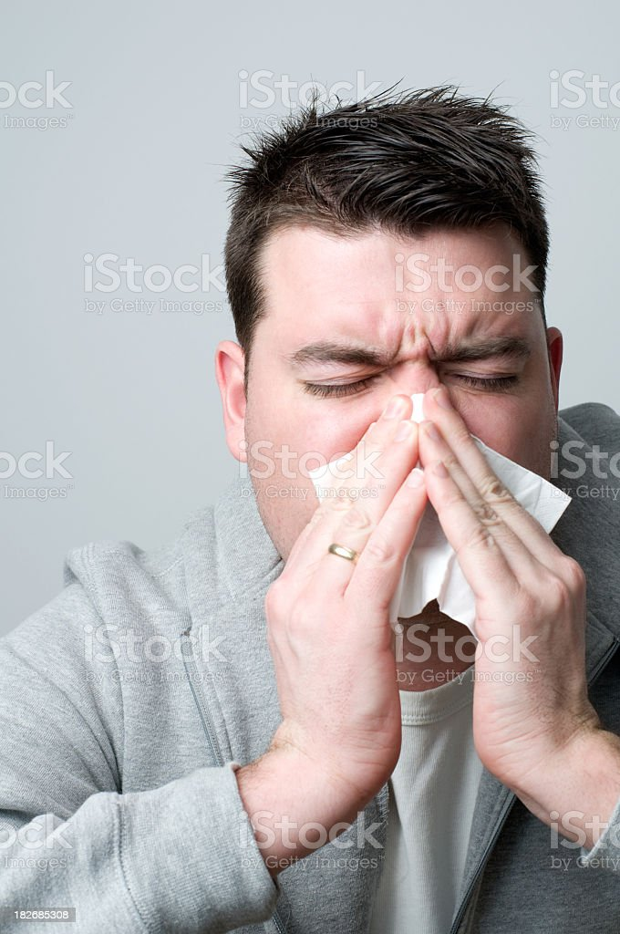 Man catches a cold and sneezes into a paper tissue royalty-free stock photo