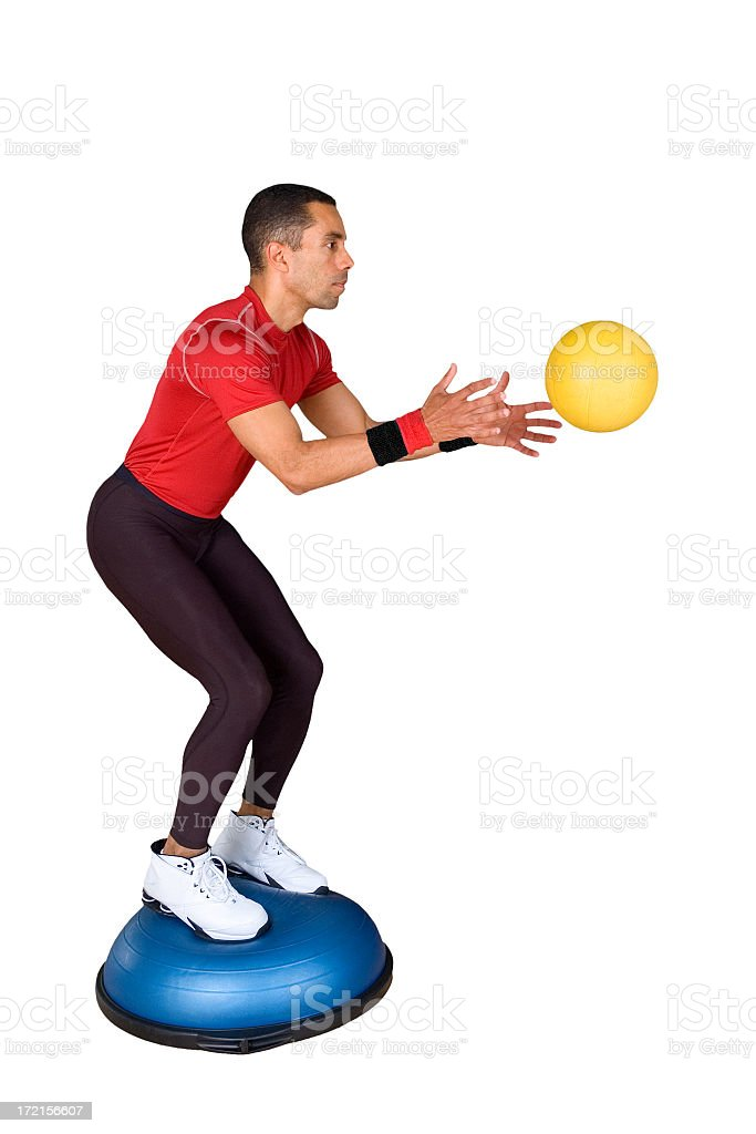 Man catching a medicine ball while on balancing trainer royalty-free stock photo