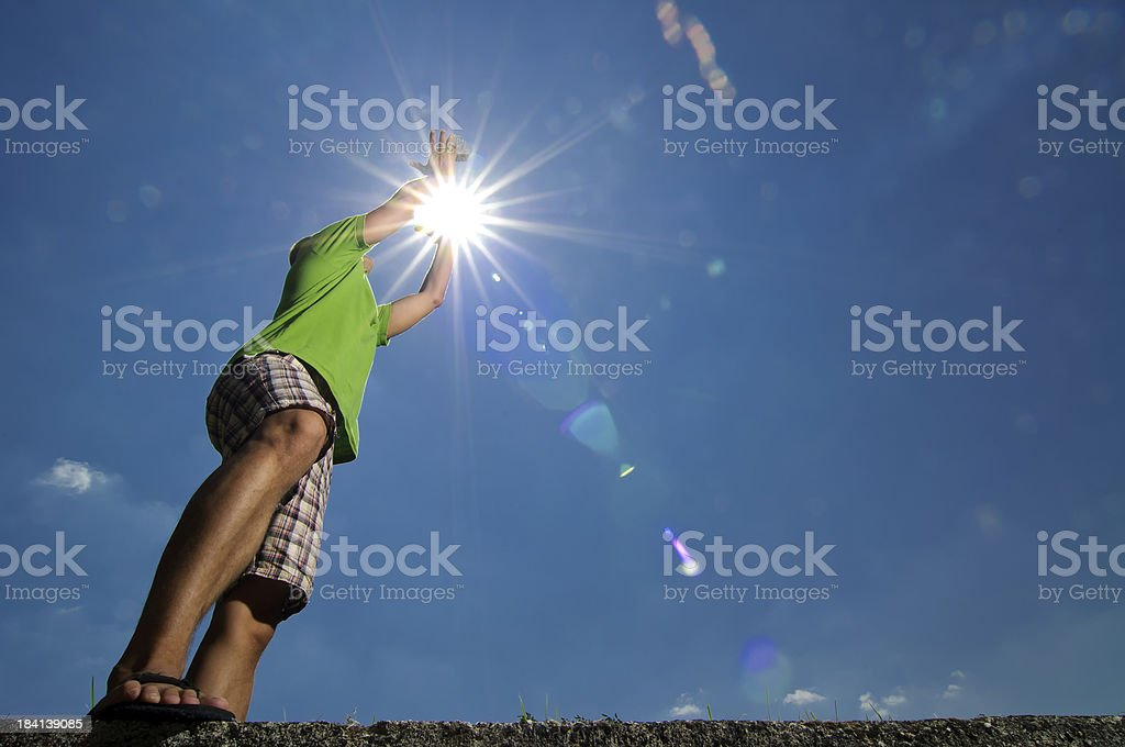 Man catching stone in sun stock photo