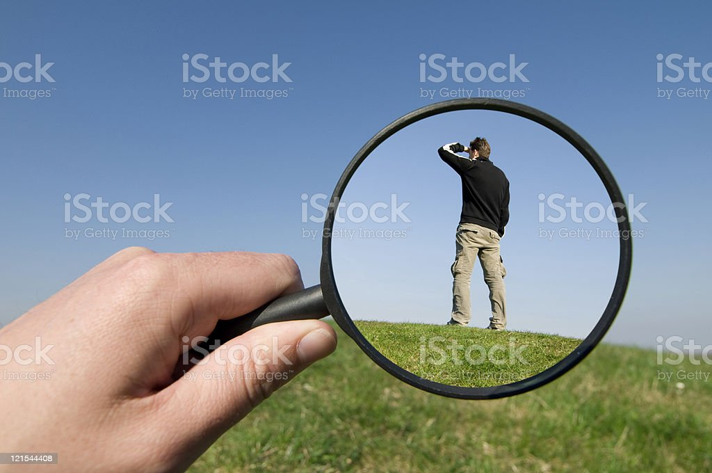 Man caught in a magnifying glass looking for something royalty-free stock photo