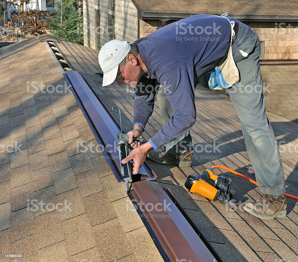 Man caulking ridge vent stock photo