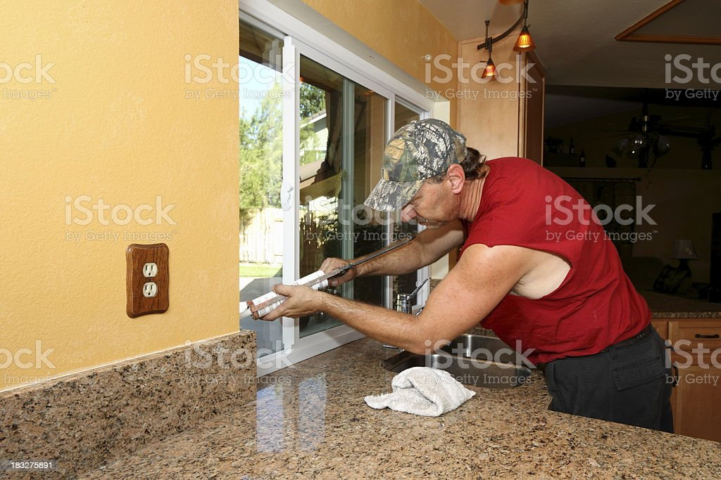 Man Caulks New Energy Efficient Windows in Kitchen royalty-free stock photo