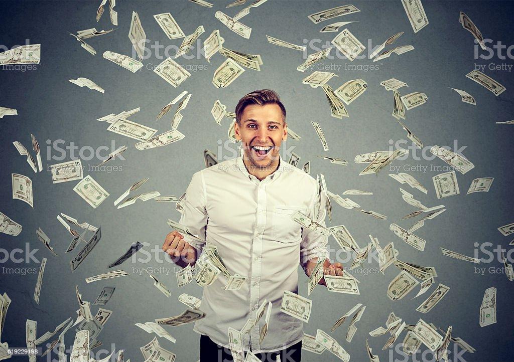 man celebrates success under money rain stock photo