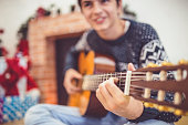 Man celebrating party at home and playing guitar