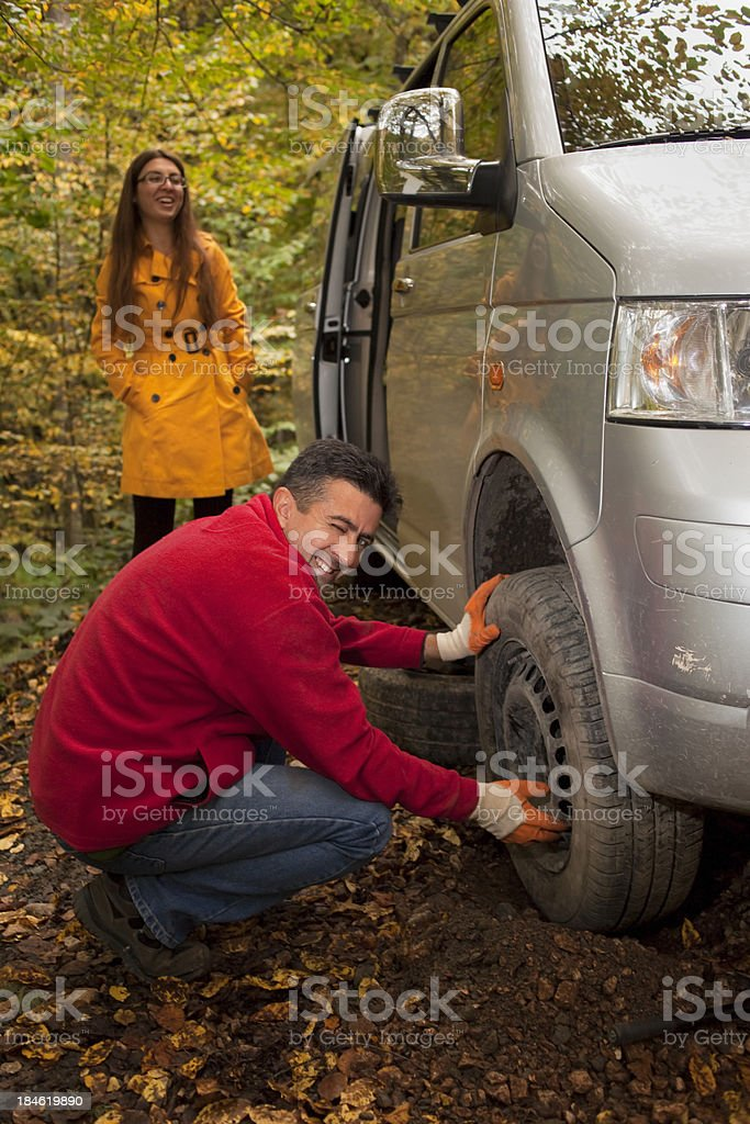 Man changed the flat tire at forest stock photo