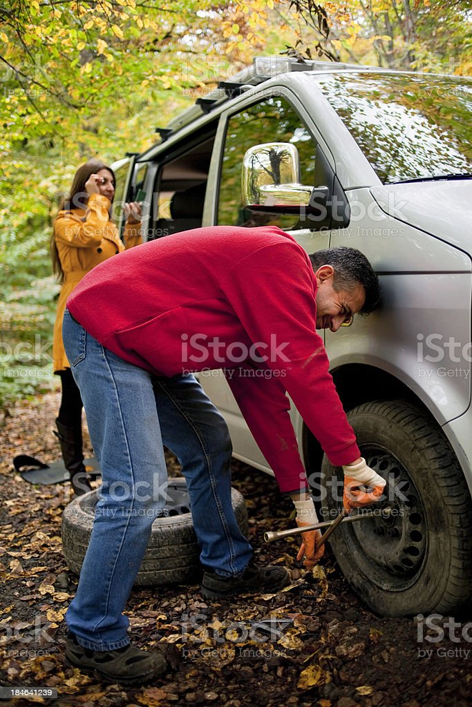 Man changed tire,  woman doing makeup royalty-free stock photo