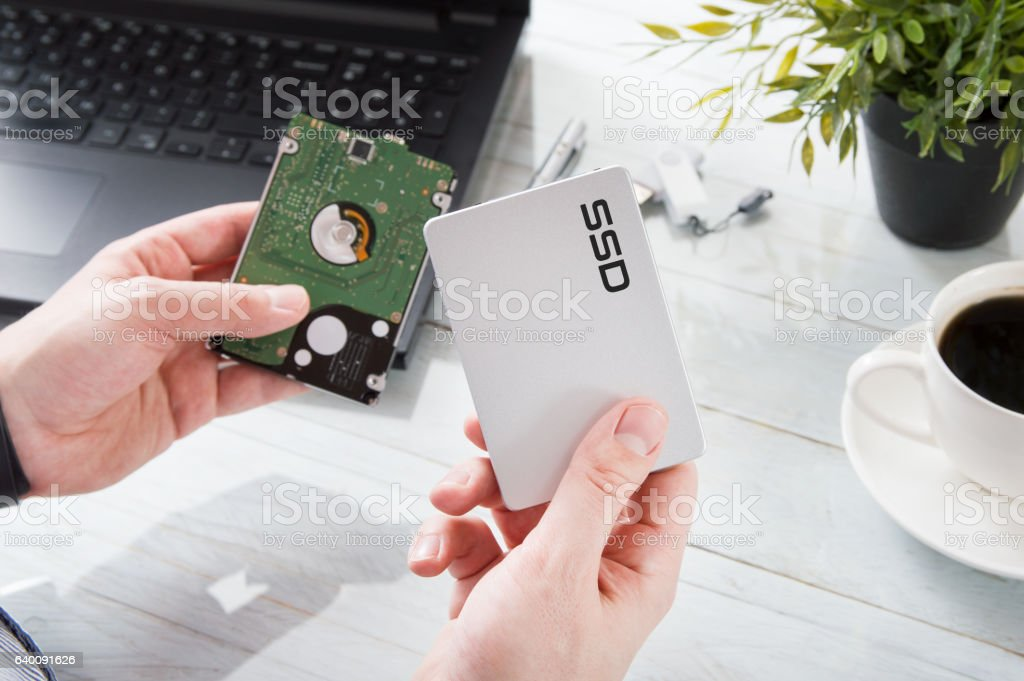 Man changes hard drive disk to a modern ssd stock photo