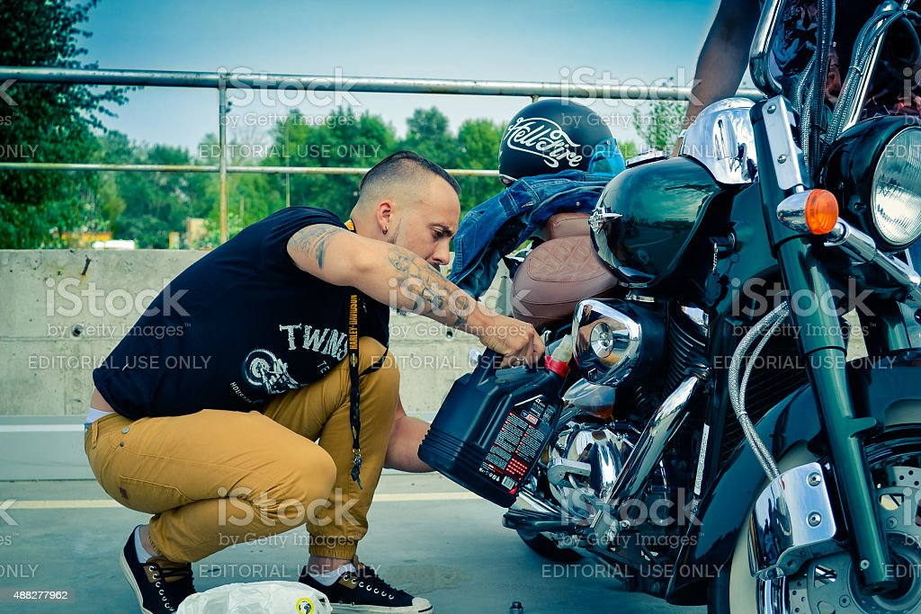Man changes the oil in Motorcycles stock photo