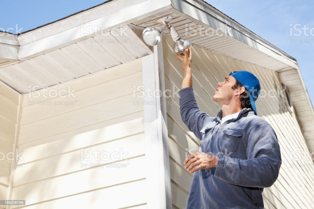 Man changing lightbulb stock photo