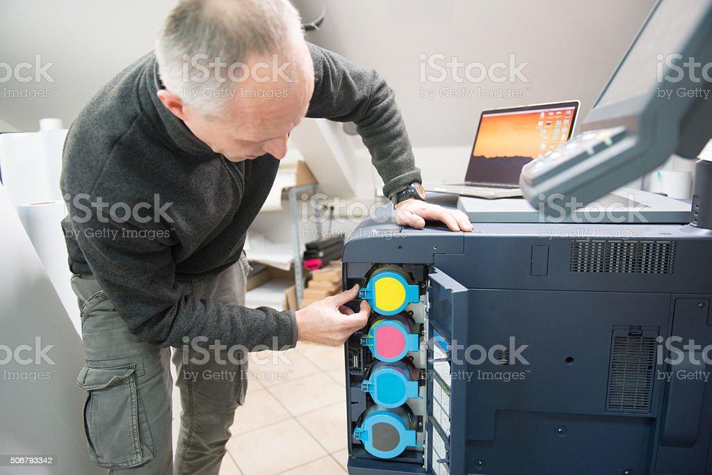 Man Changing Printer Cartridge stock photo