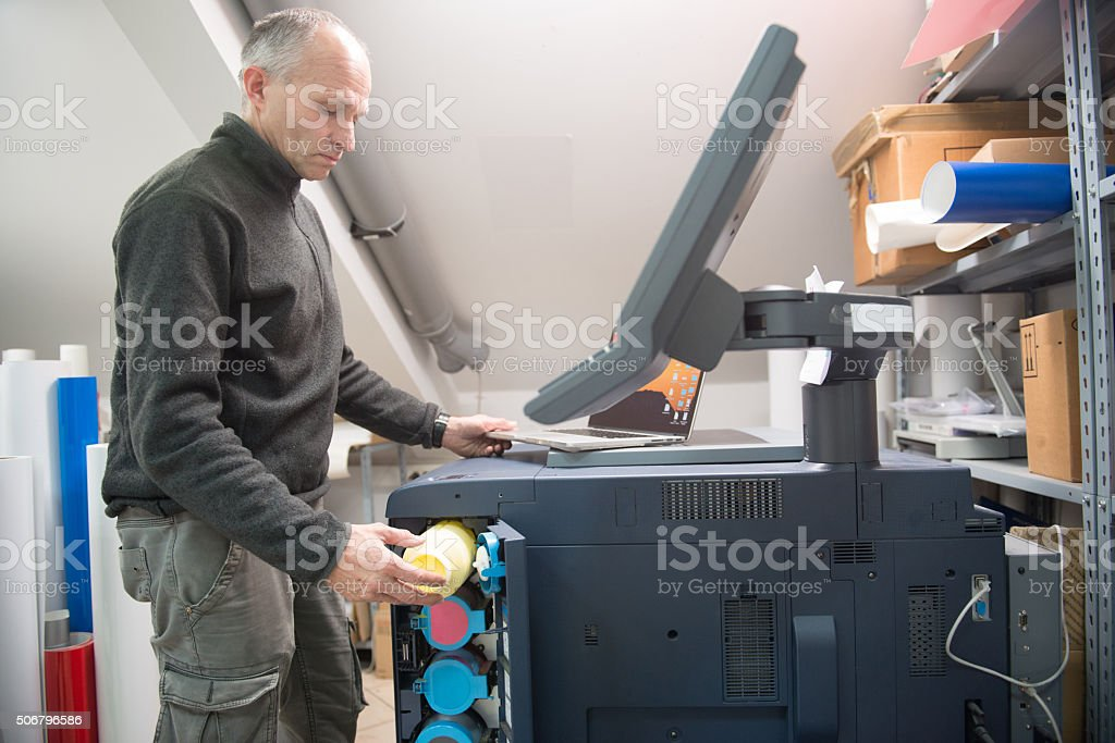 Man Changing Printer Cartridge stock photo
