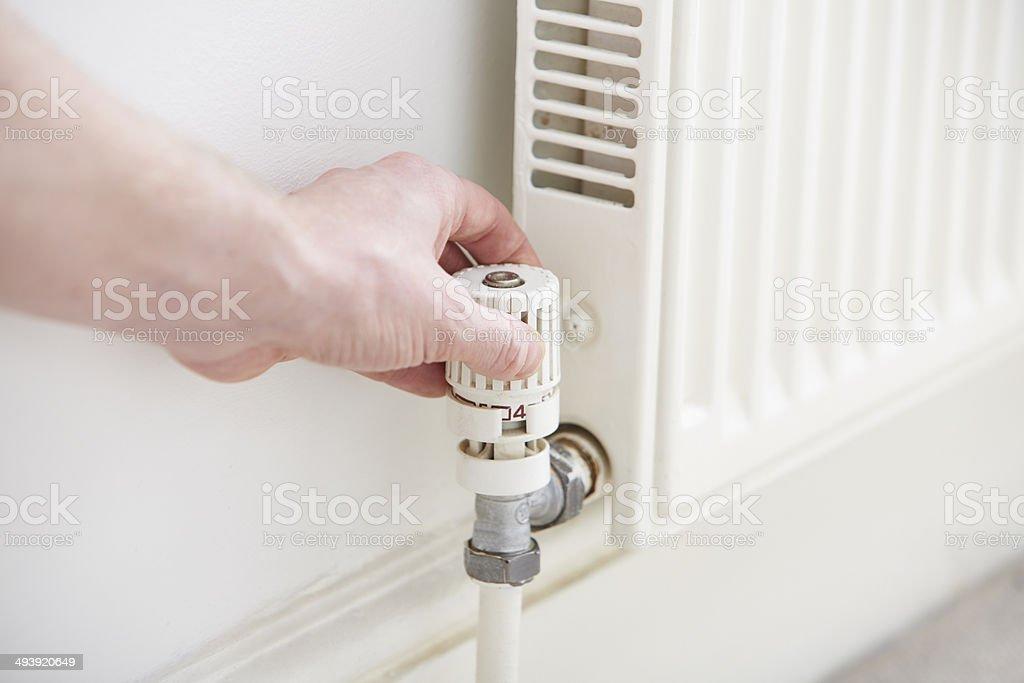 Man changing radiator thermostat stock photo