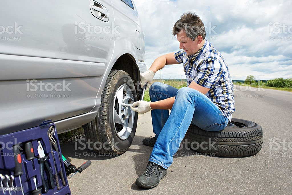 Man changing spare tire of car stock photo