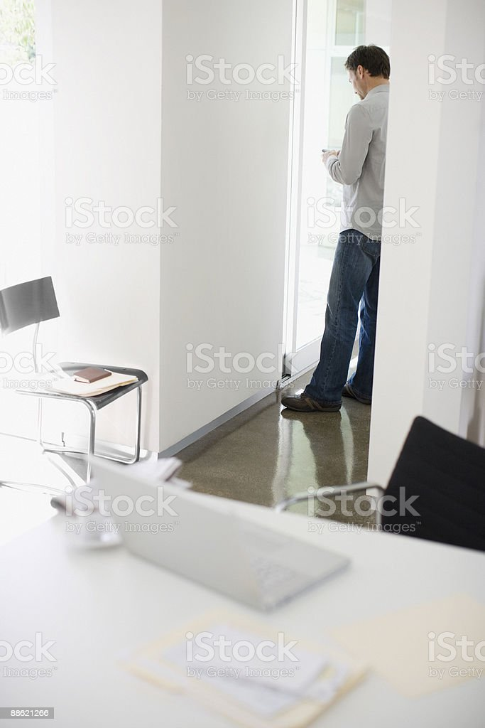 Man checking cell phone near desk royalty-free stock photo