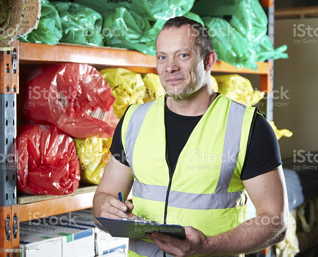 Man checking clipboard in warehouse stock photo