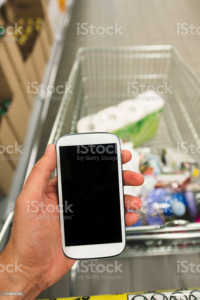 Man checking his grocery list on his smart phone royalty-free stock photo