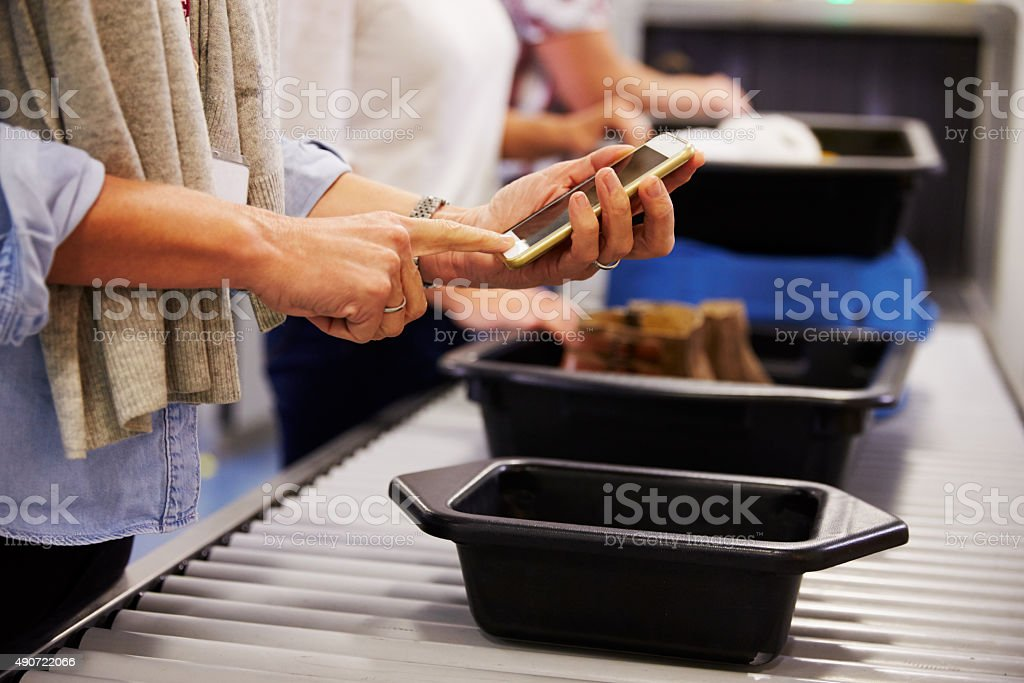 Man Checking Mobile Is Charged At Airport Security Check stock photo