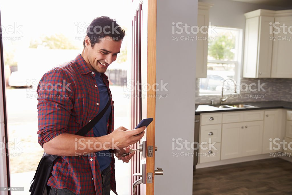 Man Checking Mobile Phone As He Opens Door Of Apartment stock photo