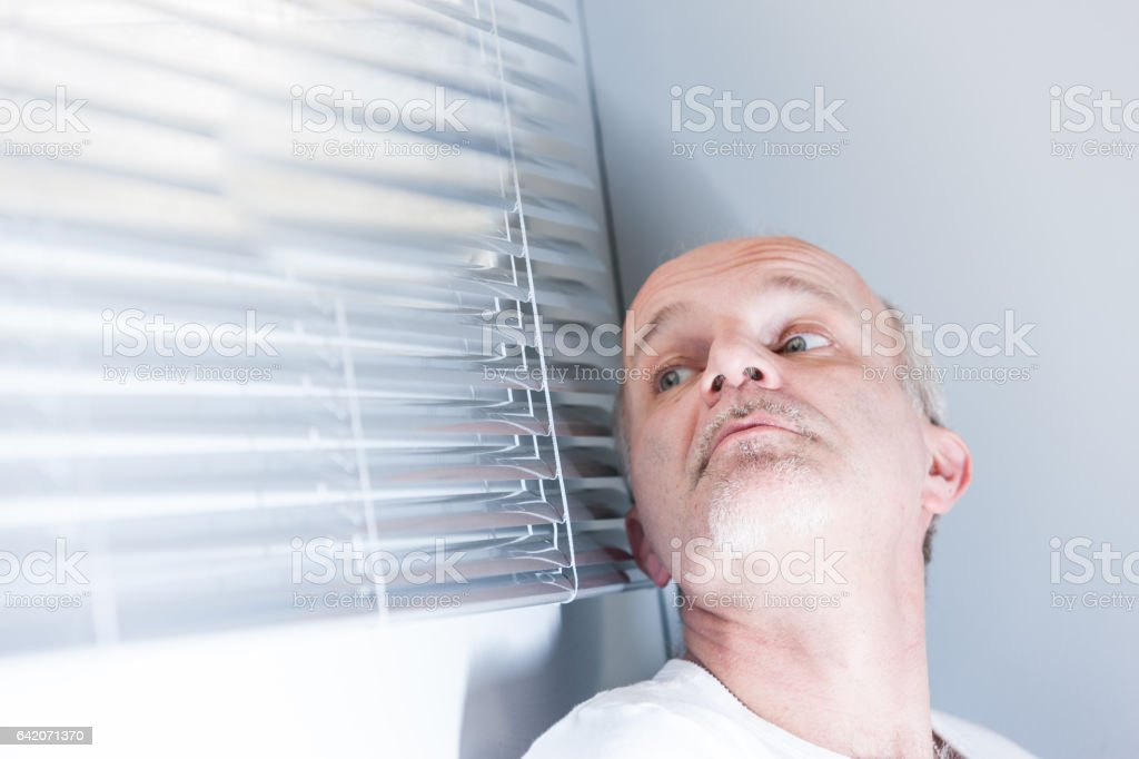 man checking out of the blinds stock photo
