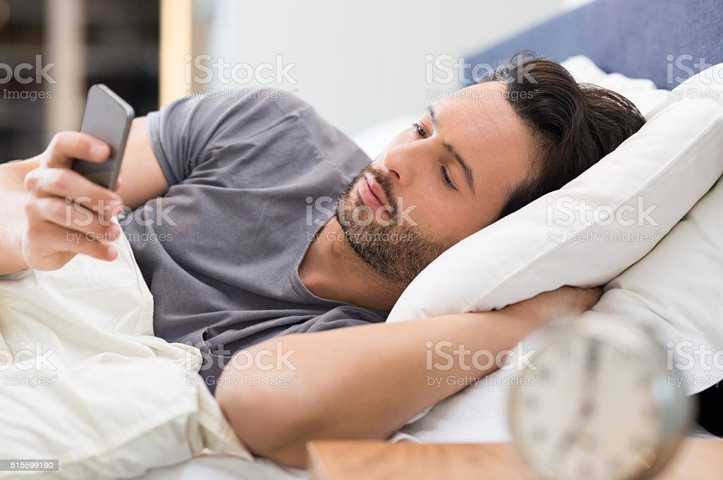 Young man checking phone on getting up in the morning. Man lying on...