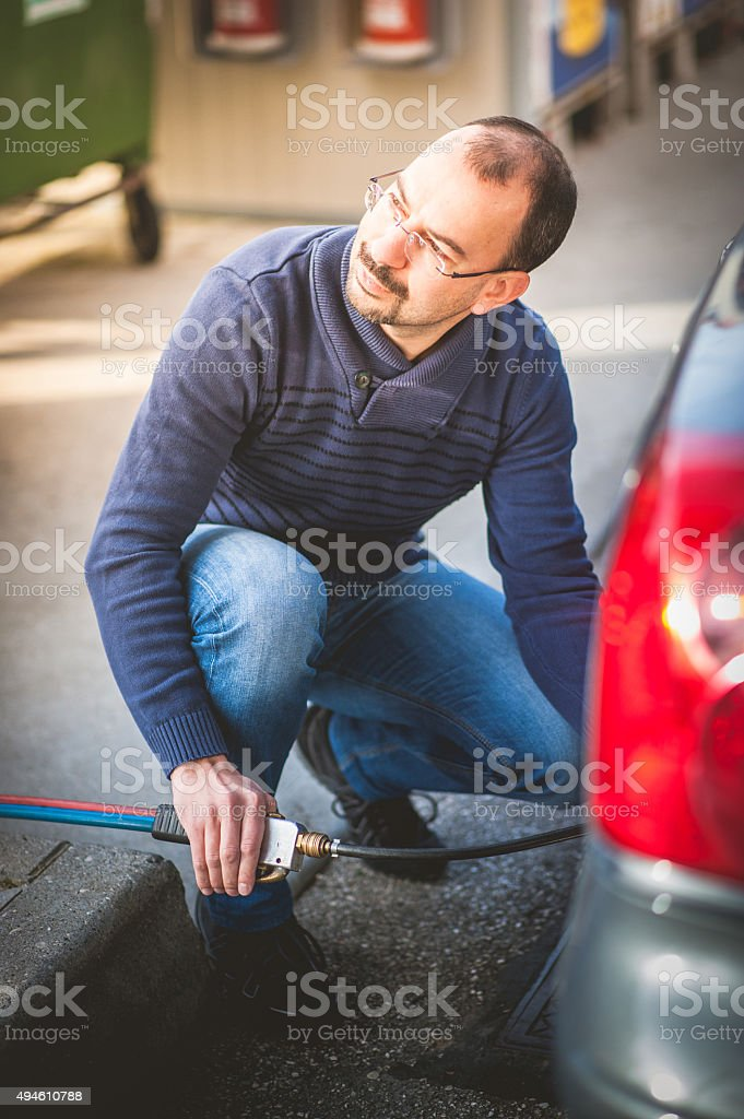 Man Checking Pressure and Inflating Car Tire stock photo
