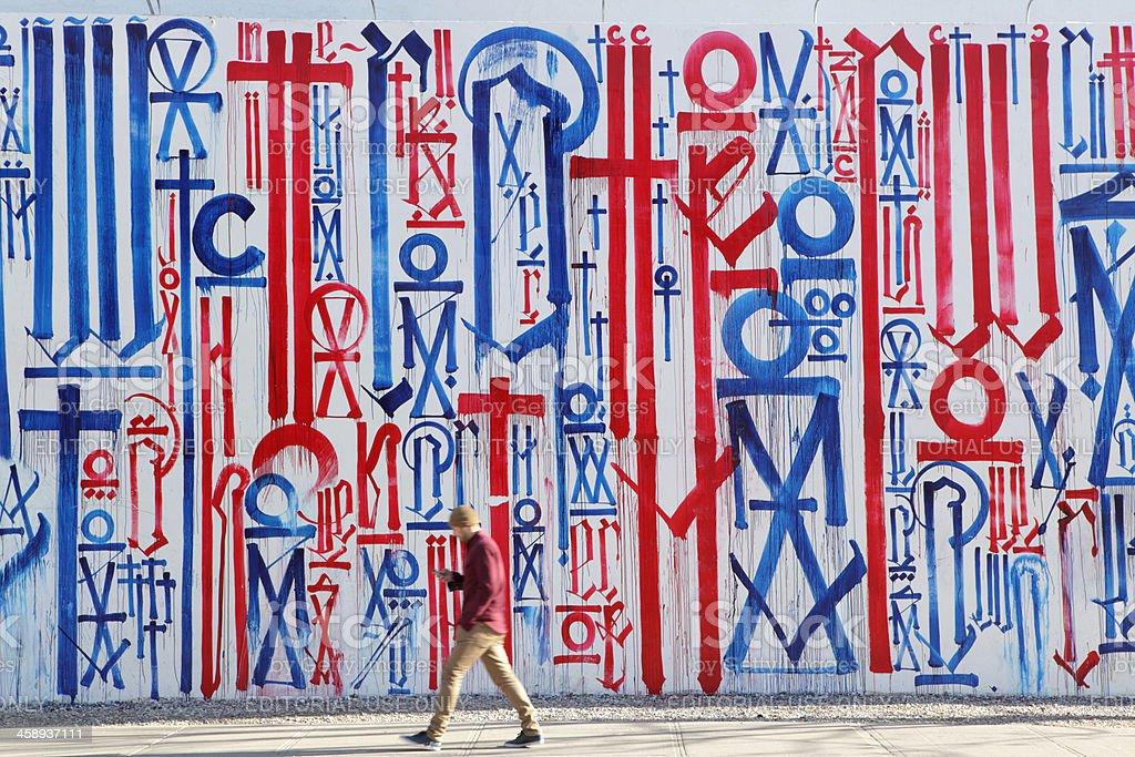 NYC man checks cell phone walking past street art mural stock photo