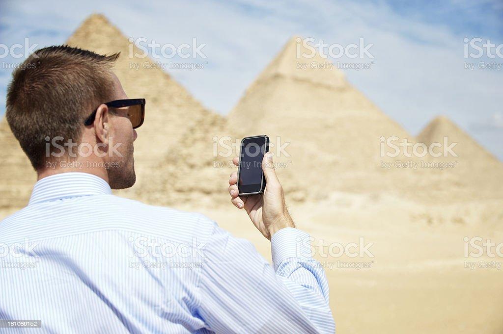 Man Checks Smartphone Next to Great Pyramids Giza Egypt royalty-free stock photo