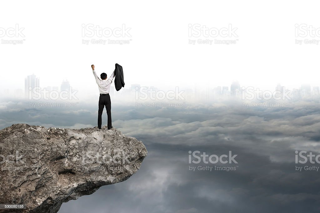 man cheering on cliff with gray cloudy sky cityscape background stock photo