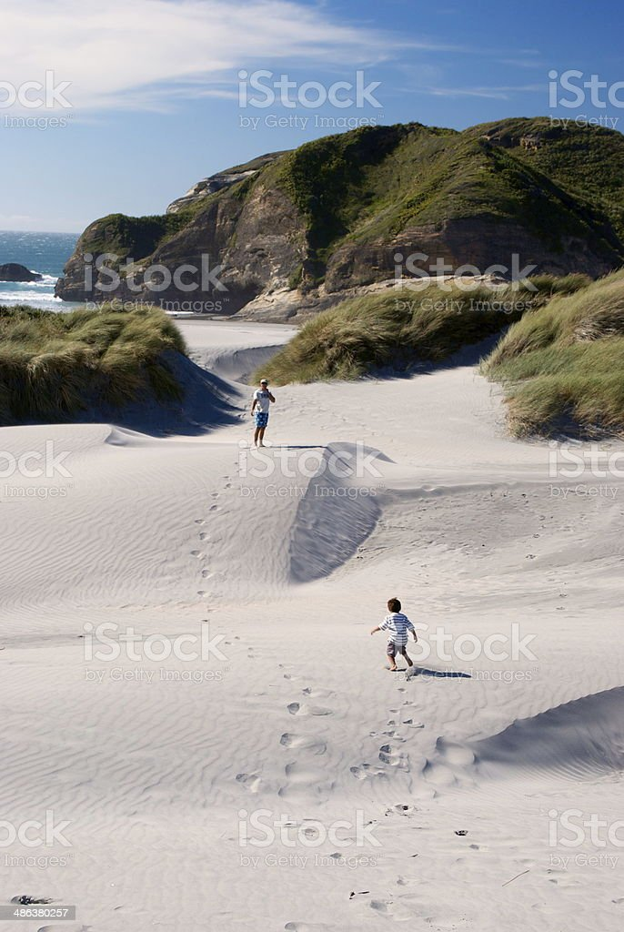 Man & Child on Sand Dunes, Wharariki Beach, NZ stock photo
