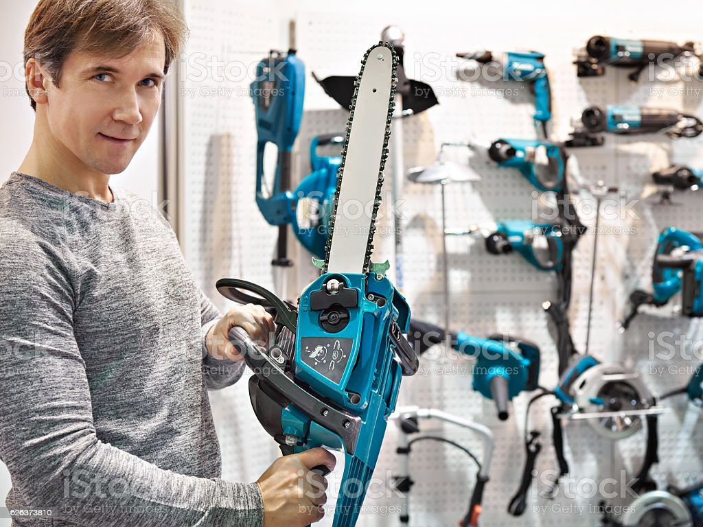 Man chooses chain saw stock photo