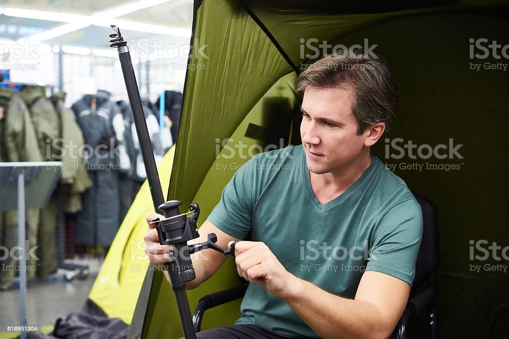 Man chooses fishing rod in shop stock photo