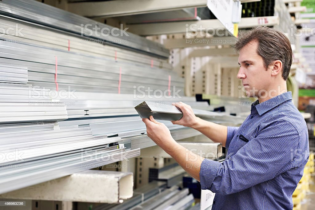 Man chooses metal profile for construction stock photo
