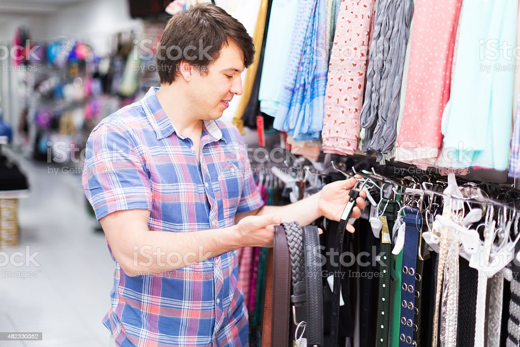 Man choosing belts in shop stock photo
