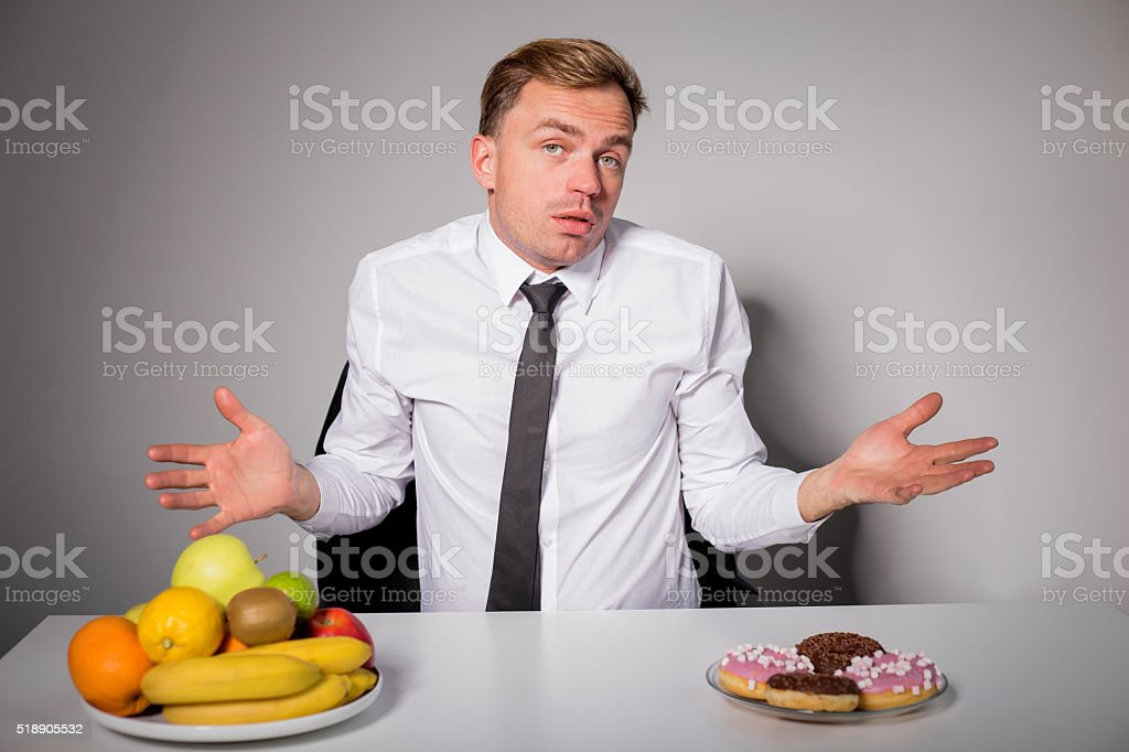 Man choosing between healthy and unhealthy food stock photo