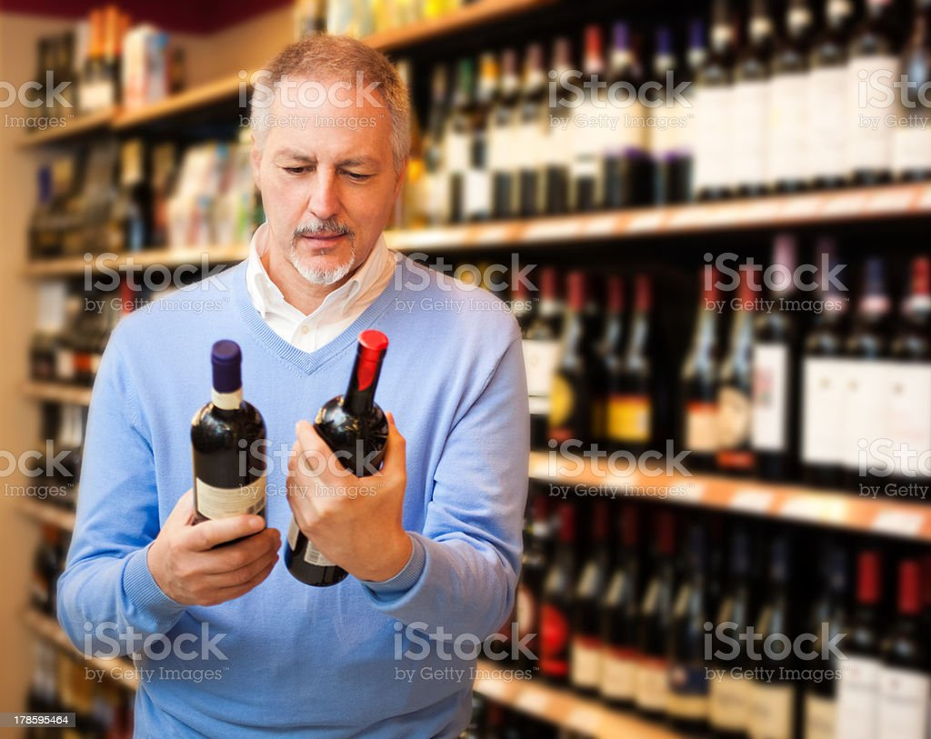 Man choosing between two bottles of wine stock photo