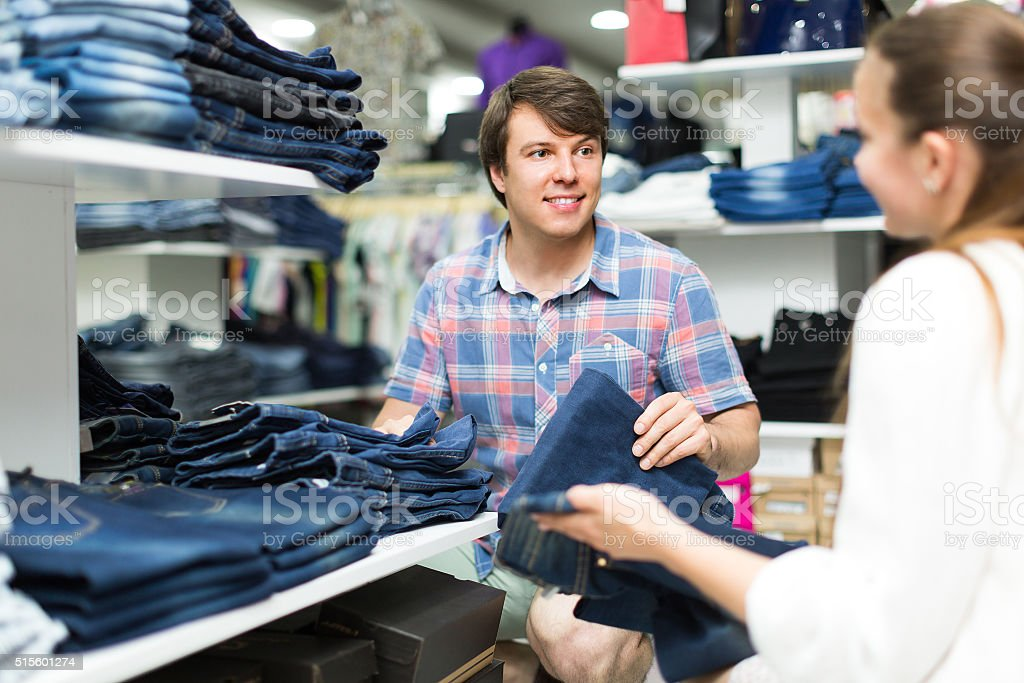 Man choosing blue jeans at the shop stock photo