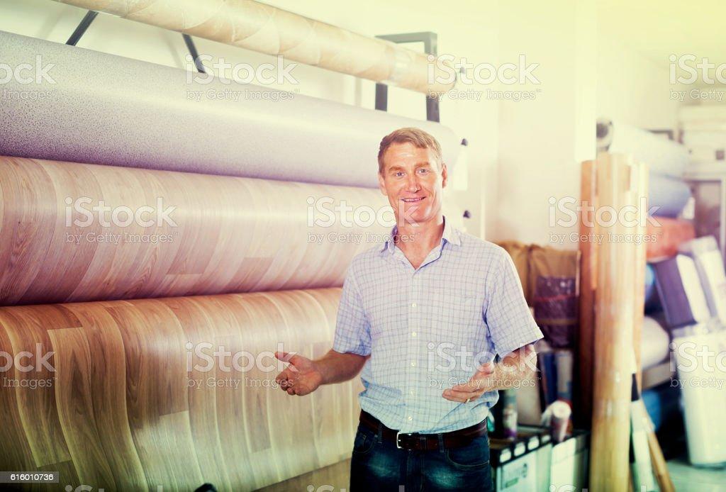 man  choosing bolt of linoleum stock photo