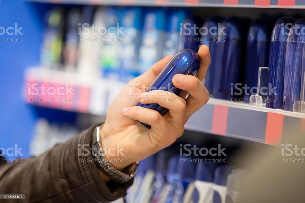 Man choosing cosmetics in supermarket stock photo