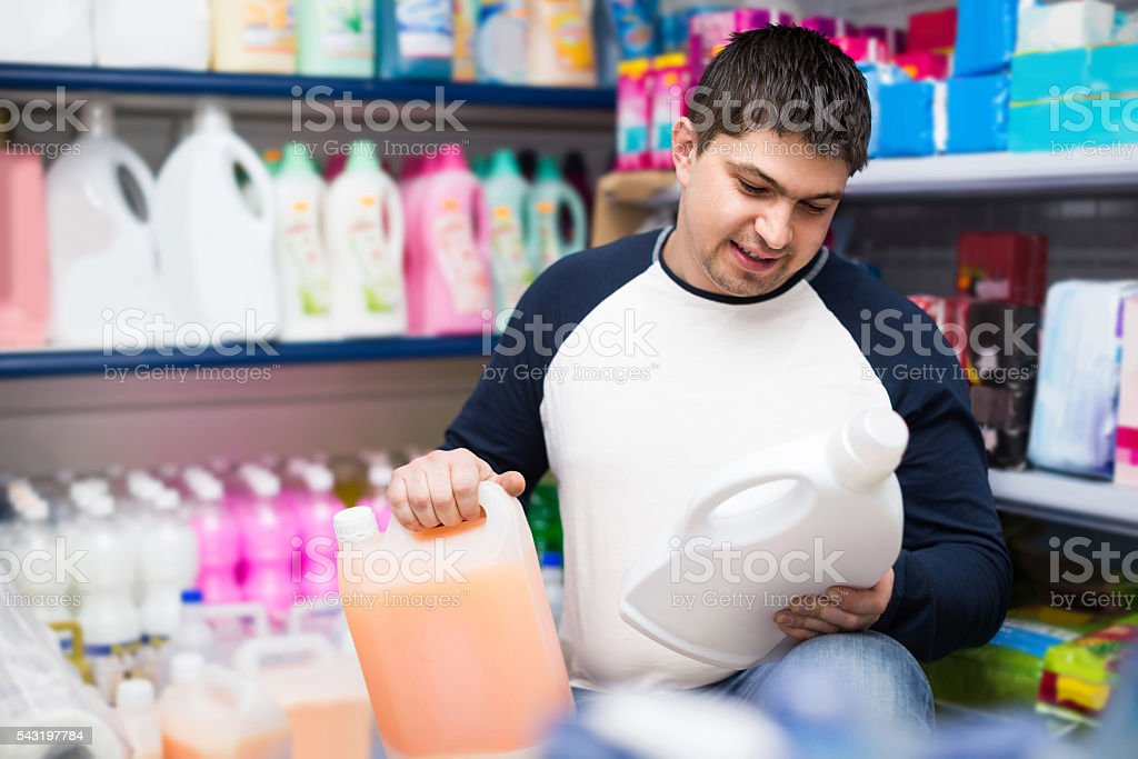 man choosing detergent in laundry section of supermarket stock photo