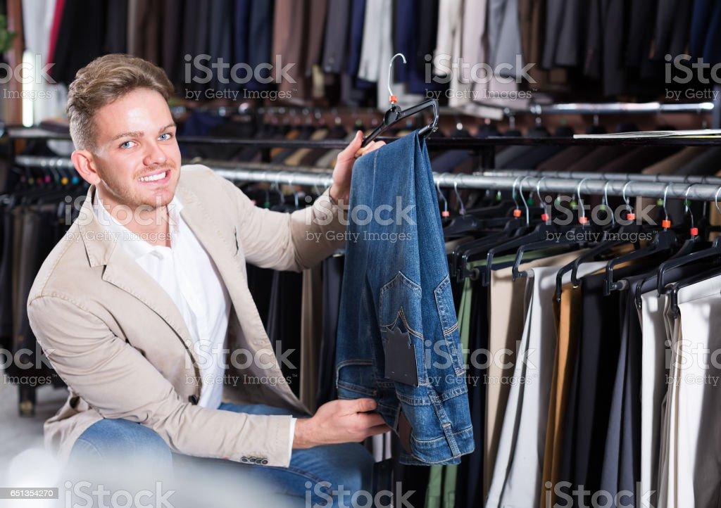 Man choosing new trousers stock photo