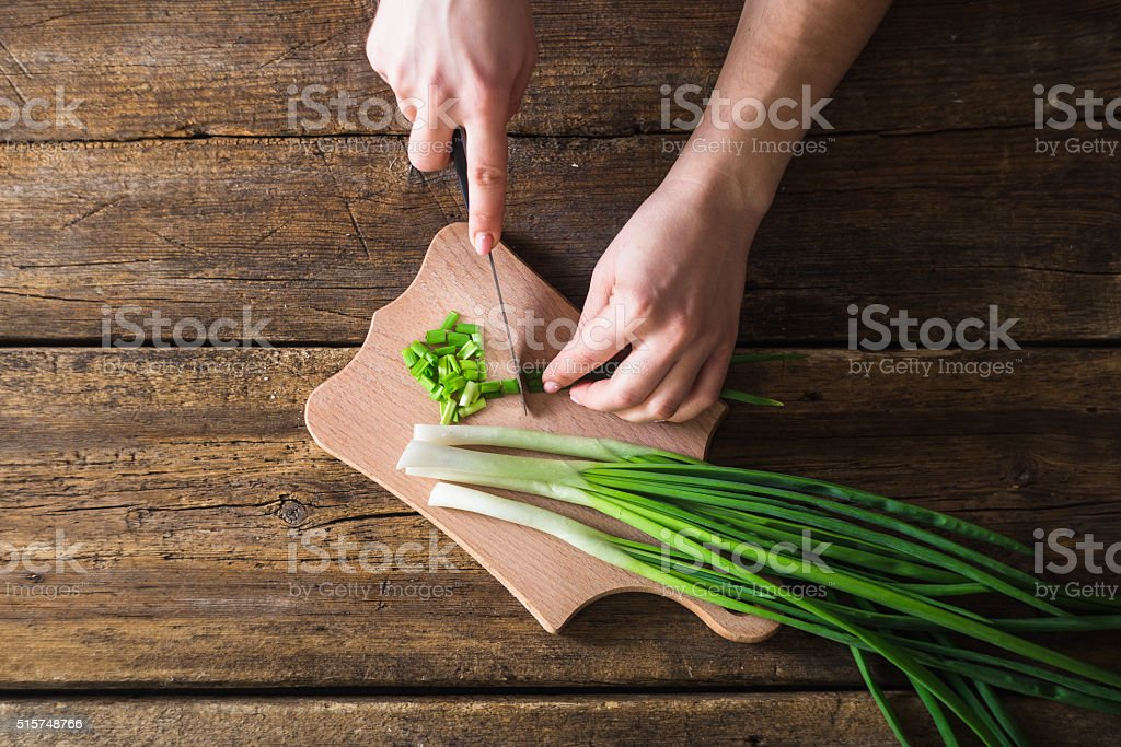 man chopped green onion on the board. Wooden table stock photo